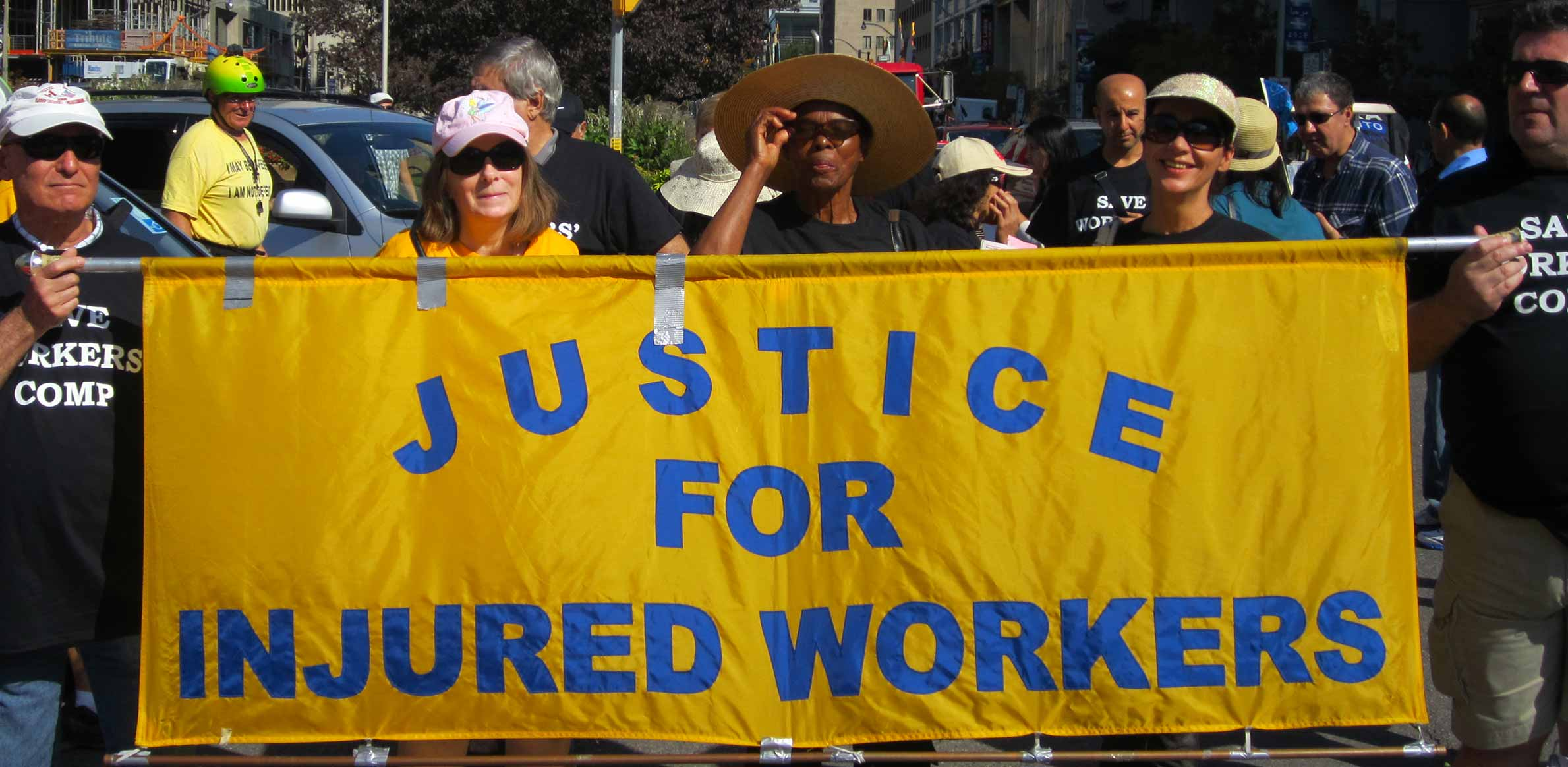 Workers hold Justice for injured workers banner on street