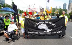 Injured Workers march behind ONIWG banner